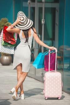 Adatti la giovane donna con i sacchetti della spesa e un bagaglio