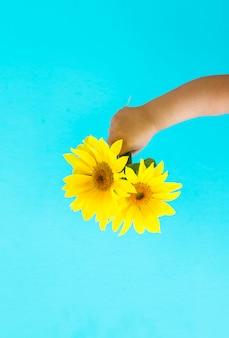 Adatti la mano di arte di un bambino piccolo che tiene il fiore giallo del sole