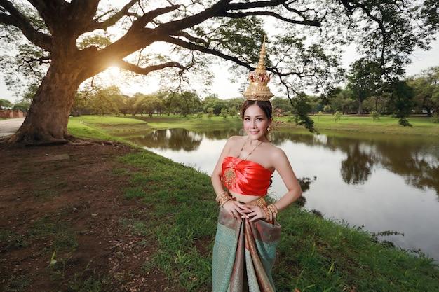 Adatti la ragazza asiatica in costume tradizionale tailandese in tempio antico con il fiore del volante a disposizione e il fronte felice