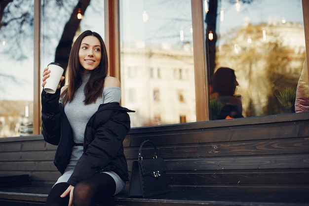 Adatti la ragazza che si siede in una città dell'estate
