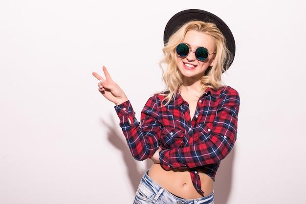 Adatti la ragazza della donna in occhiali da sole neri e black hat isolati sul rosa