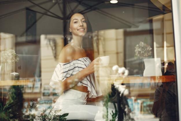 Adatti la ragazza in un caffè dell'estate