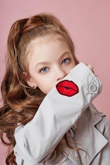 Adatti la ragazza in vestiti alla moda sul fondo colorato della parete. autunno abiti luminosi sui bambini
