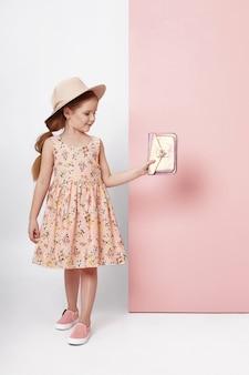 Adatti la ragazza in vestiti alla moda sulla parete colorata