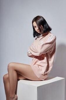 Adatti la ragazza sexy del brunette in camicia che si siede sul cubo bianco in studio. moda posa donna emozioni