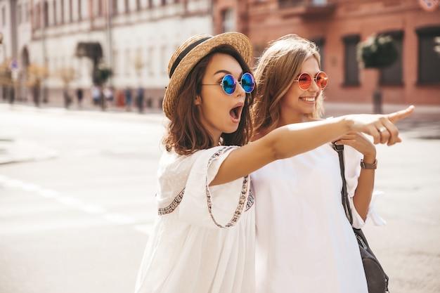 Adatti un ritratto di due donne castane e bionde di giovane giovane hippy alla moda nel giorno soleggiato dell'estate nella posa bianca dei vestiti dei pantaloni a vita bassa