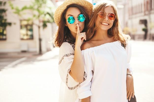 Adatti un ritratto di due giovani donne alla moda del brunette di hippy e bionde in vestito dai pantaloni a vita bassa dell'estate che posa il dito vicino alla bocca