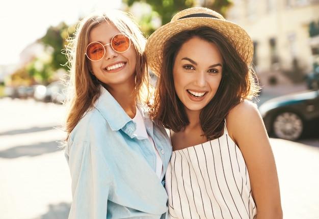Adatti un ritratto di due giovani donne sorridenti alla moda del brunette che modellano e modellano le donne nel giorno soleggiato dell'estate in vestiti dei pantaloni a vita bassa che posano sui precedenti della via