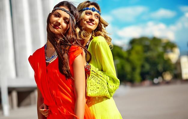 Adatti un ritratto di due giovani modelli delle donne del hippie nel giorno soleggiato dell'estate in vestiti luminosi variopinti dei pantaloni a vita bassa
