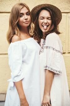 Adatti un ritratto di due modelli di donne castane e bionde del giovane hippy alla moda in vestito bianco dai pantaloni a vita bassa dell'estate che posa vicino alla parete gialla. senza trucco. mostra della lingua