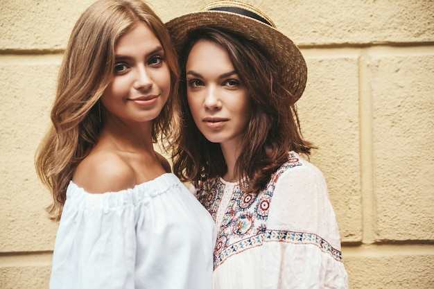 Adatti un ritratto di due modelli di donne castane e bionde di giovane hippy alla moda nel giorno soleggiato dell'estate in vestiti bianchi dei pantaloni a vita bassa che posano vicino alla parete gialla. senza trucco