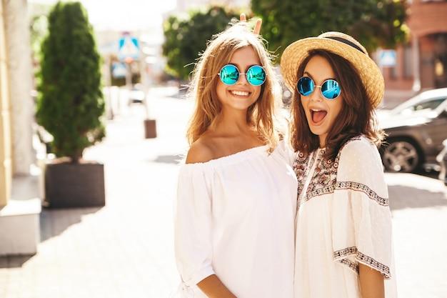 Adatti un ritratto di due modelli di donne castane e bionde di giovane hippy alla moda nel giorno soleggiato dell'estate nella posa bianca dei vestiti dei pantaloni a vita bassa. impazzendo