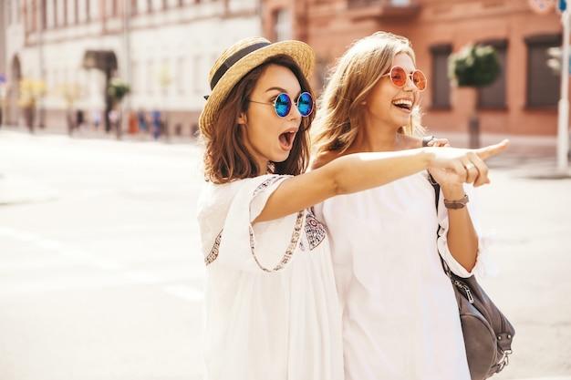 Adatti un ritratto di due modelli di donne castane e bionde di giovane hippy alla moda nel giorno soleggiato dell'estate nella posa bianca dei vestiti dei pantaloni a vita bassa. indicando sulle vendite del negozio