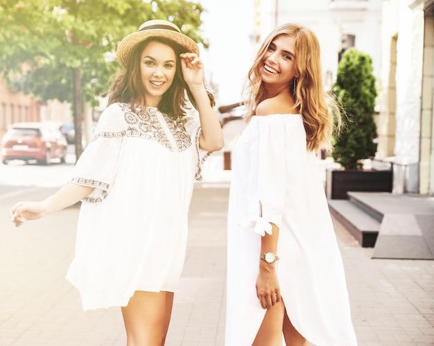 Adatti un ritratto di due modelli di donne castane e bionde di giovane hippy alla moda nel giorno soleggiato dell'estate nella posa bianca dei vestiti dei pantaloni a vita bassa. senza trucco