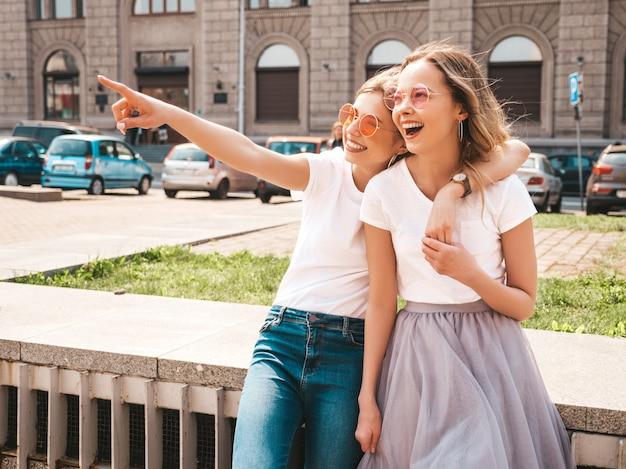 Adatti un ritratto di due modelli di donne castane e bionde di giovane hippy alla moda nel giorno soleggiato dell'estate nella posa bianca dei vestiti dei pantaloni a vita bassa