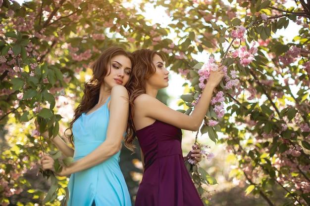 Adatti una foto del ritratto di due donne vicino all'albero sbocciante sulla natura