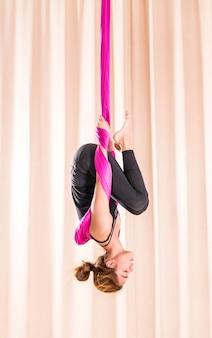 Addestramento asiatico della donna nella stanza di forma fisica con gli elementi di yoga della mosca