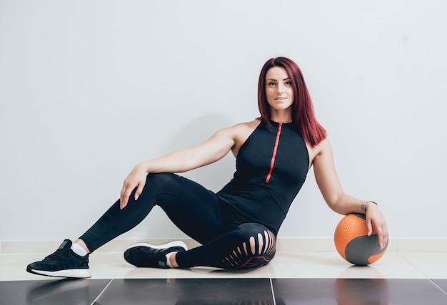 Addestramento atletico della giovane donna con il medball a gray.