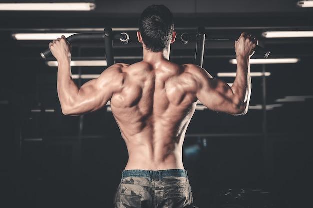 Addestramento atletico di dieta dell'uomo di potere bello che pompa su i muscoli di schiena