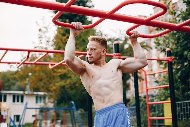 Addestramento bello dell'uomo in un parco di estate
