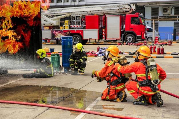 Addestramento dei vigili del fuoco con abbigliamento protettivo che spruzza acqua ad alta pressione al fuoco