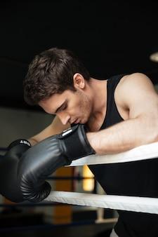 Addestramento del pugile in un ring. guardando da parte.