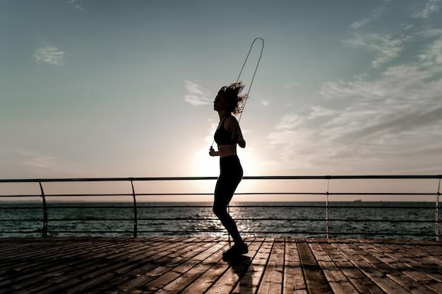 Addestramento dell'adolescente con una corda di salto sulla spiaggia