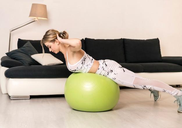 Addestramento della donna a casa sulla palla di forma fisica