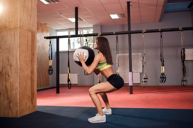 Addestramento della donna con ginnastica funzionale in palestra