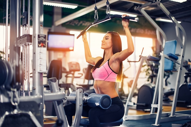 Addestramento della donna con la macchina di addestramento di sollevamento pesi