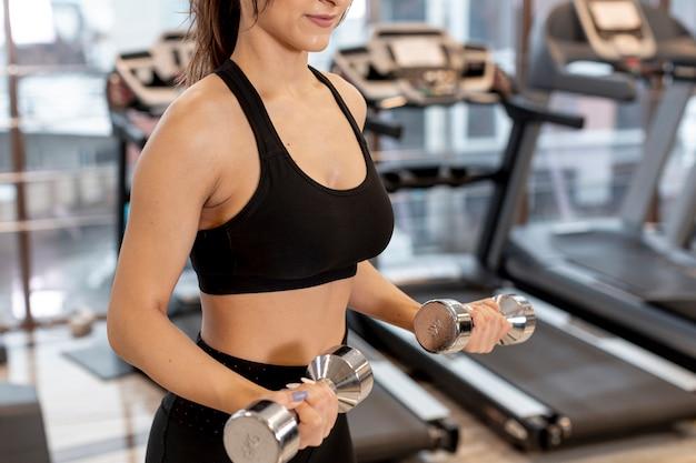 Addestramento della donna del primo piano con i pesi