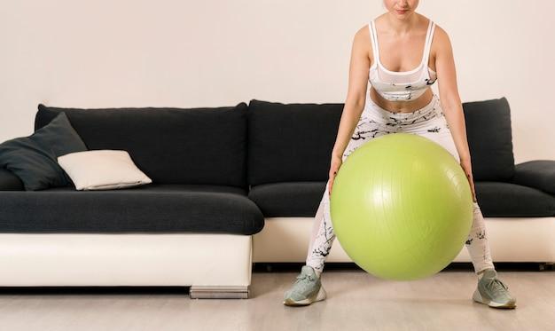 Addestramento della donna del primo piano con la palla di forma fisica