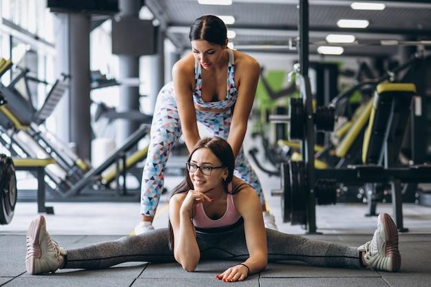 Addestramento della donna in palestra con istruttore di fitness femminile