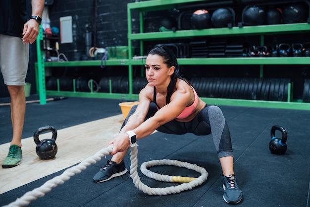Addestramento della giovane donna con la corda di battaglia in una palestra del crossfit