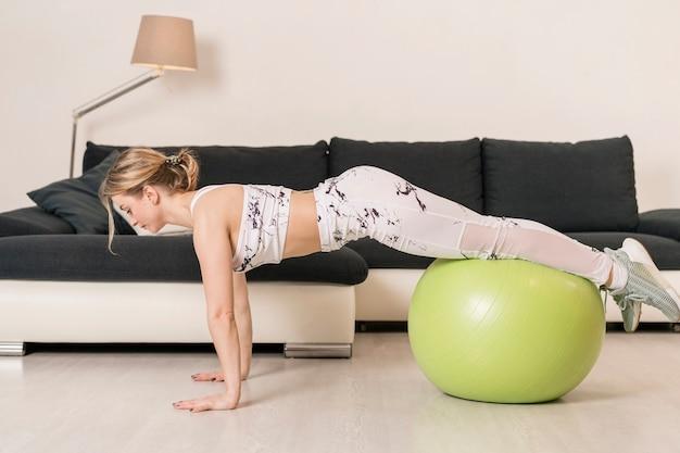 Addestramento della giovane donna con la palla di forma fisica