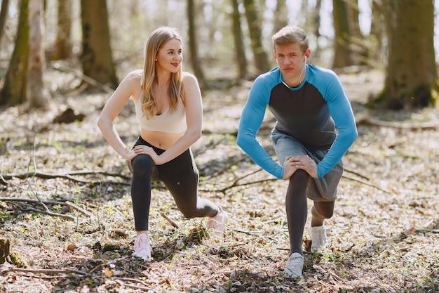 Addestramento delle coppie di sport in una foresta di estate