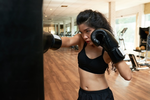 Addestramento femminile del pugile nella palestra in guantoni da pugile