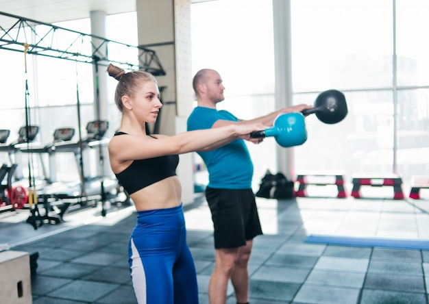 Addestramento funzionale doppio. uomo sportivo e donna adatta che fanno esercizio con kettlebell in palestra