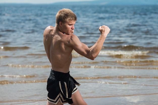 Addestramento muscolare combattente maschio. il pugile si allena all'aria aperta