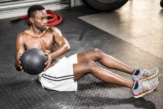Addestramento muscolare dell'uomo con la palla medica alla palestra del crossfit