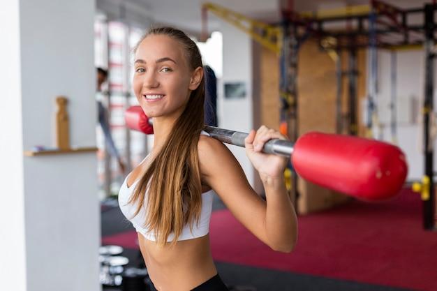 Addestramento sorridente della donna con la barra di peso