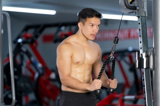 Addestramento sportivo dell'uomo che fa esercizio nella palestra di forma fisica