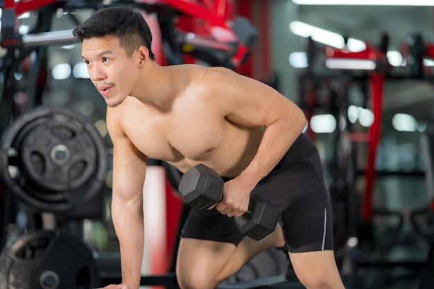 Addestramento sportivo dell'uomo con la testa di legno in palestra