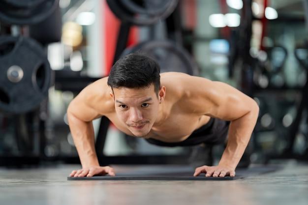 Addestramento sportivo dell'uomo facendo flessioni in palestra