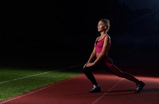 Addestramento sportivo della ragazza sullo stadio alla notte dopo avere corso.