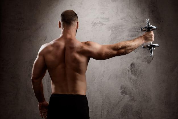 Addestramento sportivo potente giovane con manubri sul muro scuro.