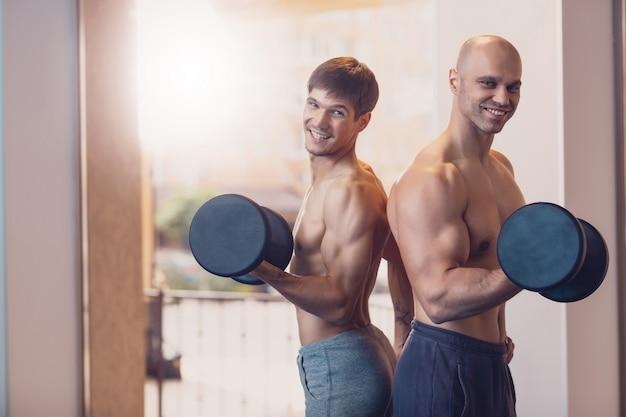 Addestrando due uomini con i manubri i muscoli del braccio