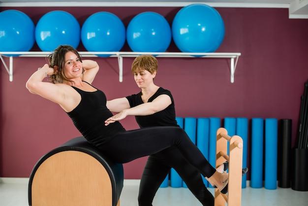 Addestratore personale che controlla donna che allunga su un barilotto della scala dei pilates