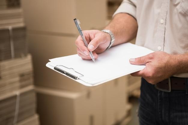 Addetto al magazzino che controlla il suo elenco negli appunti