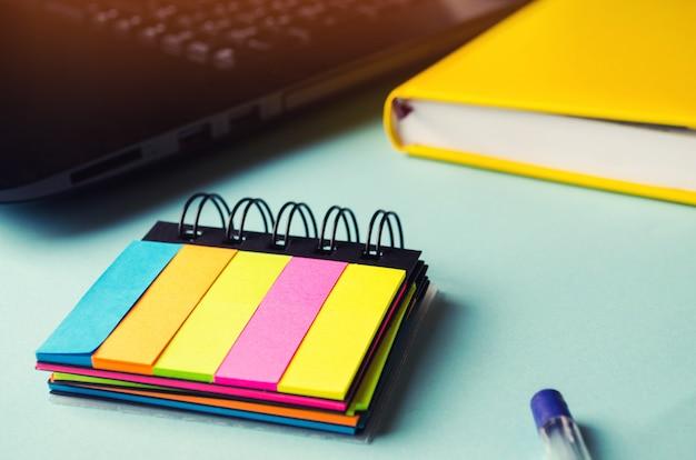 Adesivi appiccicosi sul tavolo, desktop, note, piani per il giorno, laptop, concetto di scuola.